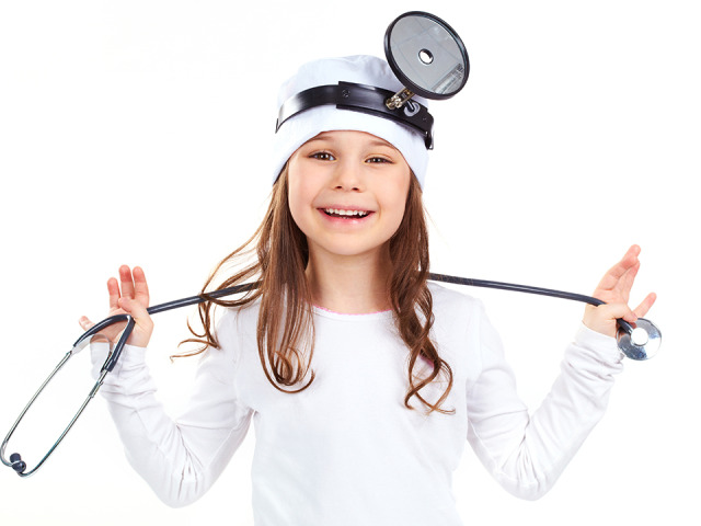 Cute little girl dressed like a doctor looking at camera with a
