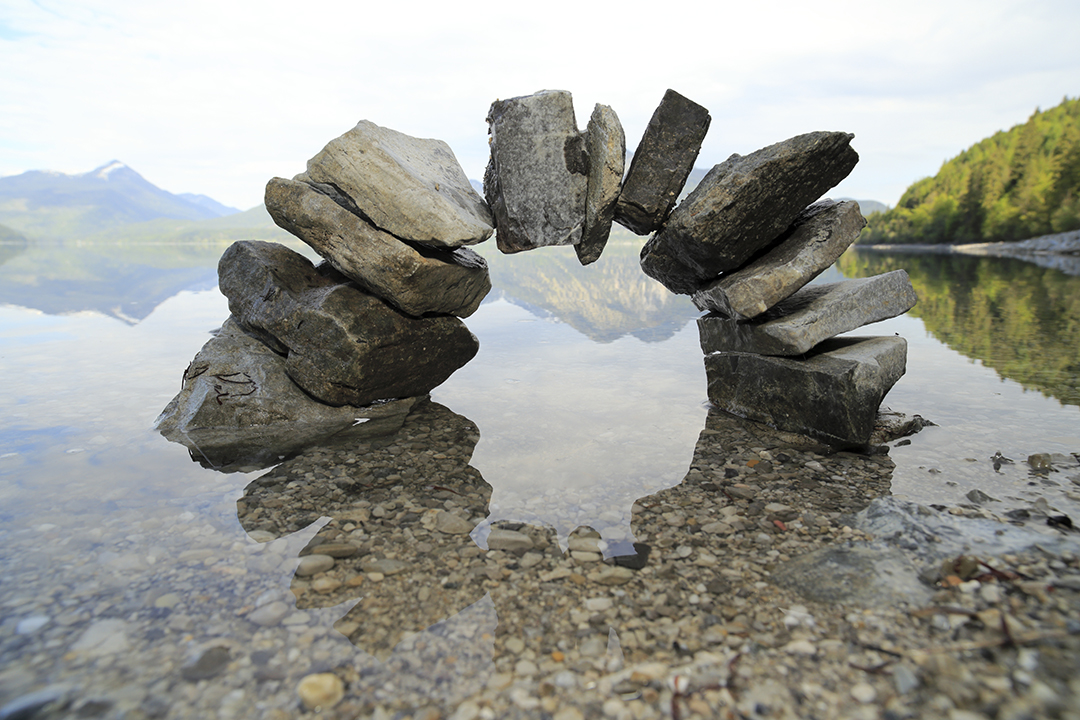 a bridge with stones and lake background