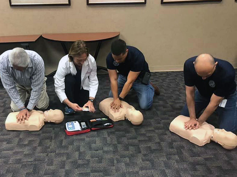Dr. Scott Crawford, second from left, used medical manikins to instruct attendees on the proper way to provide CPR and demonstrated how to operate an automated external defibrillator (AED) device.