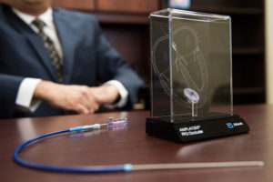 A display model of an Amplatzer septal occluder and a catheter tube.