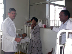 Donald Meier, M.D. (left), speaks with a medical resident (right) and patients in a hospital in Ethiopia in this undated photo. (Photo courtesy of Donald Meier)