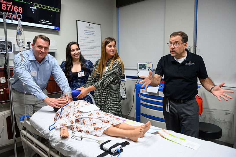 Brian Wilson, right, a faculty associate faculty associate in the Department of Emergency Medicine's Division of Simulation Education at the TECHS center, instructs a group of visitor in the use of a medical manikin.