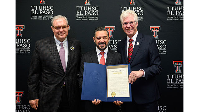 Texas State Rep. César Blanco (D-El Paso), center, presents a resolution to commemorate the 10-year anniversary of the Paul L. Foster School of Medicine to TTUHSC El Paso President Richard Lange, M.D., M.B.A. (right). At left is El Paso Mayor Dee Margo.