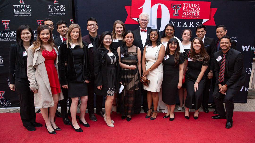 "Students from the Paul L. Foster School of Medicine Joined TTUHSC El Paso President Richard Lange, M.D., M.B.A., on the red carpet before the ""Red Tie Affair for a White Coat Occasion"" gala to celebrate the 10-year anniversary of the Paul L. Foster School of Medicine."